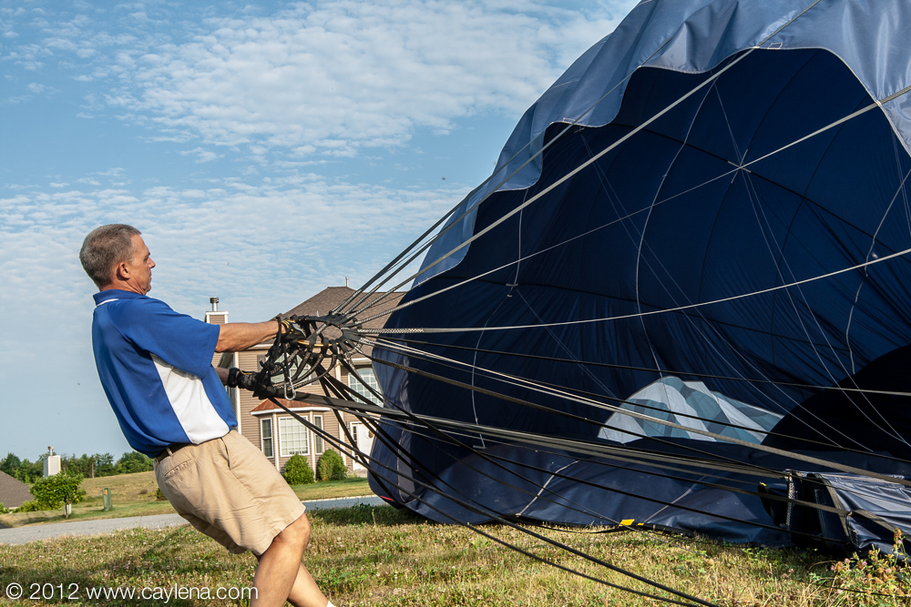 Gary Dunlap, of SkyCab Balloon Promotions in Louisville, KY, assists with the deflation of the balloon after the morning flight in Poughkeepsie, NY. (July 7, 2012)