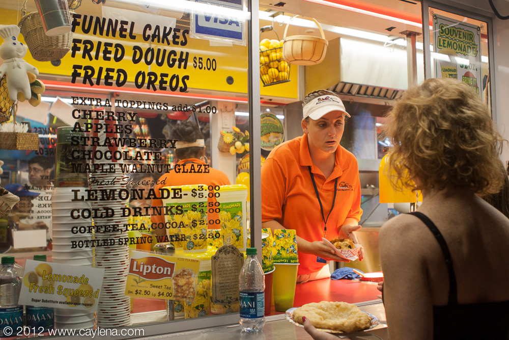 Jenna Perry, of Buffalo, a 15-year employee of Debbie's Fried Dough, from Wilmington, NC, serves fried dough and deep fried oreos to a customer at the Dutchess County Fair in Rhinebeck. (Aug. 24, 2012)