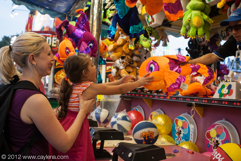 Jen Urciuoli, of Poughkeepsie, holds her daughter, Samantha, 4, as she grabs the prize she just won Friday at the Dutchess County Fair in Rhinebeck. (Aug. 24, 2012) Photo by CC Photo & Media, published in Newsday