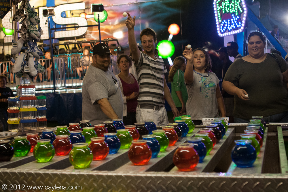 Abigail Bates (second from the right), 9, of Wallkill, prepares to throw the shot that won her a new goldfish at the Dutchess County Fair in Rhinebeck. (Aug. 24, 2012)