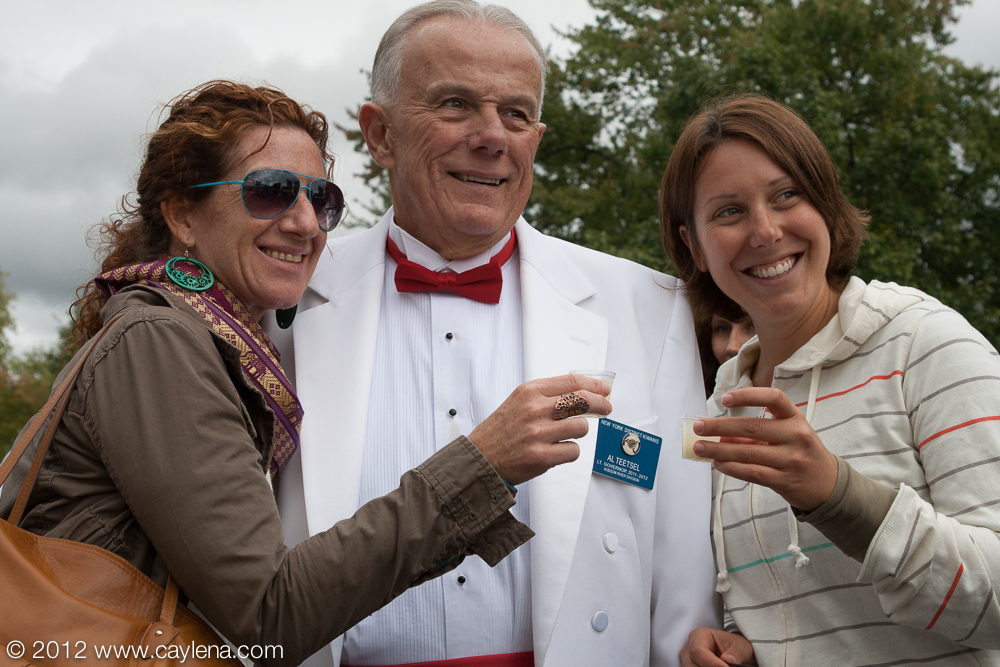 "Michelle Abarbanel and Megan Kolvenbach of Milford, Pa, pose with Al Teetsel, the 2011-12 Lt. Governor of the Hudson River Division of the Kiwanis Club, before they take their quintessential ""garlic shooter"" Saturday during the Garlic Festival in Saugerties. (Sept. 29, 2012)"