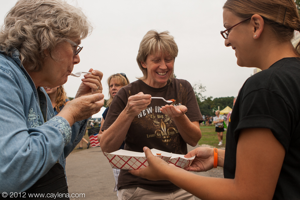 Natalie Tomasello of Rosendale, employee of Jack's Down Home Barbecue, offers barbecue sauce samples to Diane Schultz of Decatur and Linda Pappalardo of New Paltz at the Hudson Valley Rib Fest in New Paltz. (August 19, 2012)
